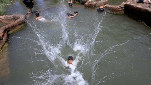 Afghan children cool off at a pond to escape the heat on a hot day in Herat, Afghanistan