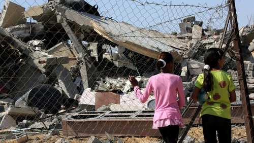 Palestinian girls inspect the rubble of a destroyed house following an Israeli airstrike in Rafah refugee camp, Gaza