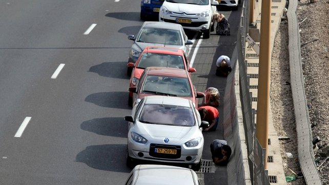 Israelis lay on the ground and take cover near their cars while sirens sound over the city of Tel Aviv, Israel