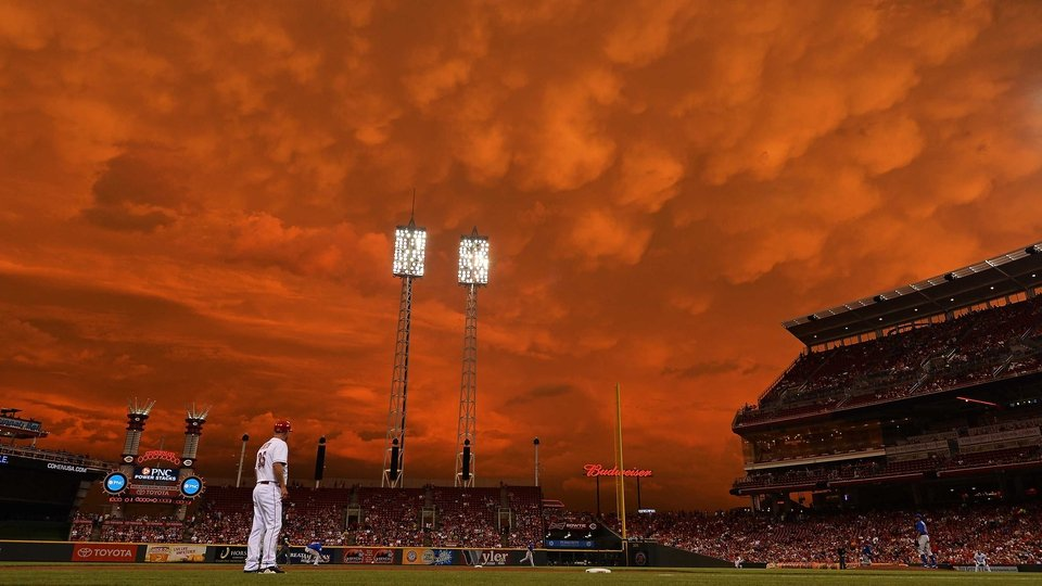 Storm clouds blanket the sky over Great American Ball Park as Starlin Castro #13 of the Chicago Cubs fields a ground ball in the fifth inning against the Cincinnati Reds