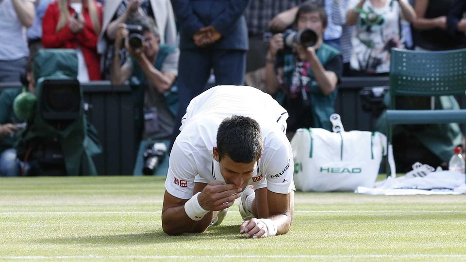 Novak Djokovic celebrates beating Roger Federer to win Wimbledon by eating the grass