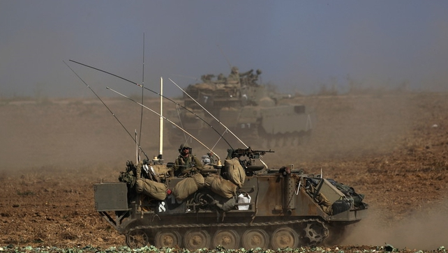 Israeli military vehicles patrolling near the Israeli border with Gaza