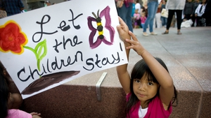 Tala Socco, six, holds a sign during a vigil and rally in support of the flood of undocumented Central American minors apprehended in Texas