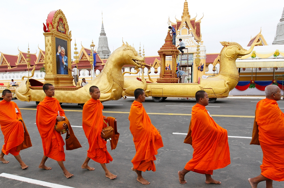 Cambodian Buddhist monks walk past a portrait of former King Norodom Sihanouk, during a ceremony in Phnom Penh, Cambodia