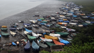 Anchored fishing boats are covered with tarpaulins at the Arabic Sea shore at the Chowk Dongri village in Thane, near Mumbai, India