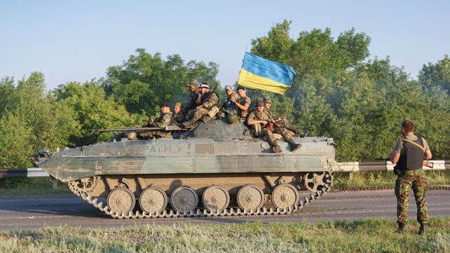 Ukrainian government forces sit atop an armoured vehicle 20km south of Donetsk