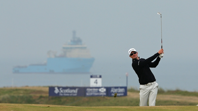 Justin Rose of England hits his approach shot on the 16th hole