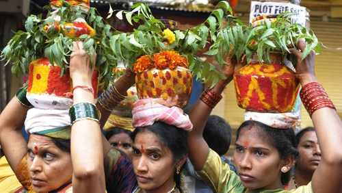 Hindu devotees carry pots for the festival of Bonalu