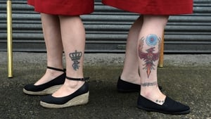 Women with loyalist themed tattoos wait for the start of Orange Order parades in Northern Ireland