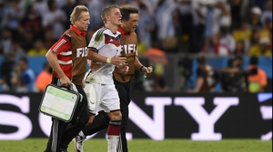 Germany midfielder Bastian Schweinsteiger left the pitch to get patched up after a rough knock that left him bleeding profusely