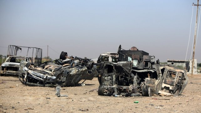 Burned and destroyed Iraq military vehicles are seen on a road in the town of Samarra