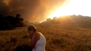 A woman reacts as a forest fire threatens the town of Keratea, 45 km southeast of Athens, Greece
