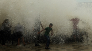 Indian schoolchildren enjoy getting splashed by breaking waves during high tide at the sea front in Mumbai