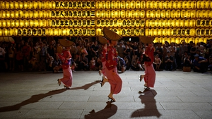 Young women perform an 'Awa Odori' dance next to lit lanterns during the annual Mitama festival at Yasukuni Shrine in Tokyo