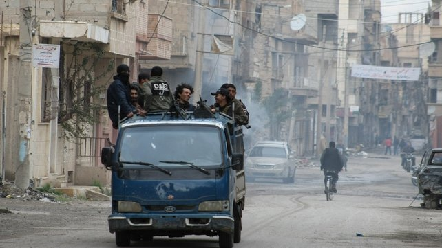 Rebels stand on the back of a pick-up truck driving through the eastern Syrian town of Deir Ezzor in March
