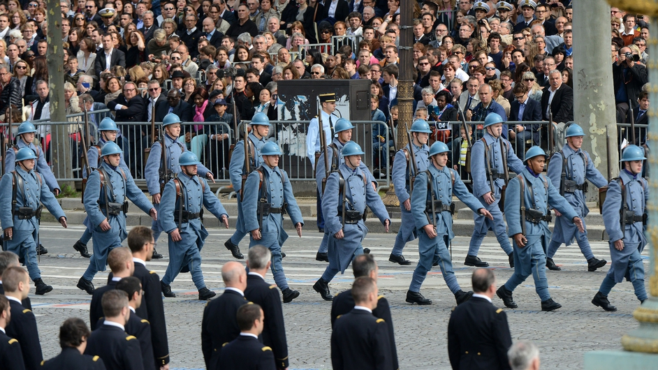 French soldiers dressed in WWI uniforms march down the Champs-Elysees