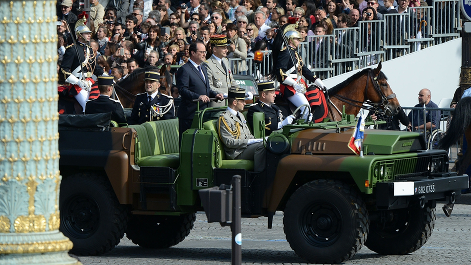 French president Francoise Hollande stands in a command car driving down the Champs-Elysees