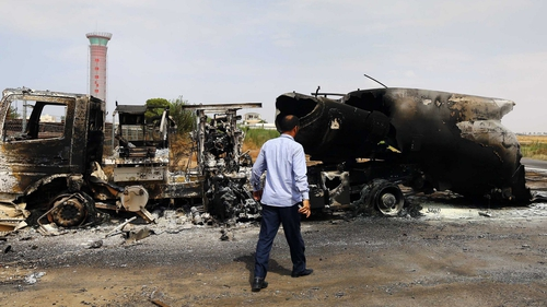 The wreckage of a truck and an airplane are seen at Tripoli international airport in the Libyan capital