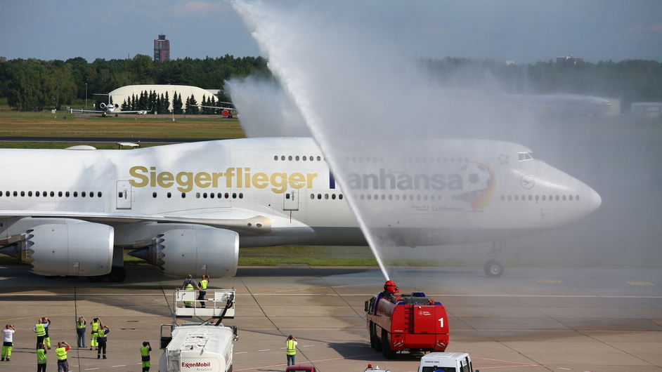 A plane carrying the German soccer champions is given a special salute from the airport fire brigade in Berlin