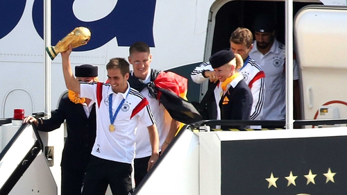 Germany's captain Philipp Lahm holds the World Cup aloft as he gets off an airplane at Berlin airport Tegel