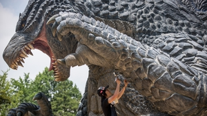 A worker puts the final touches to a Godzilla statue in Tokyo, Japan