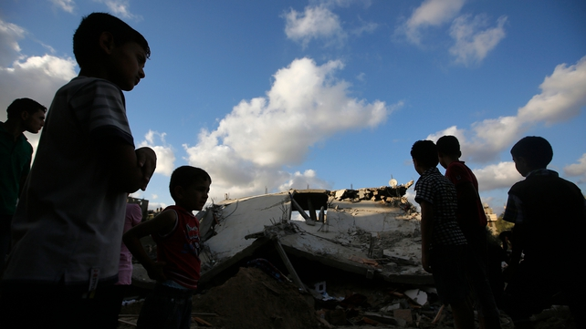 Children stand near a destroyed house following an Israeli air strike in Beit Lahiya, northern Gaza