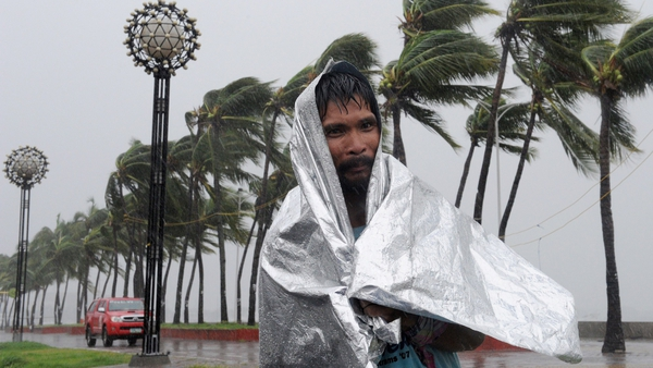 A man walks through heavy wind and rain as Typhoon Rammasun barrels across Manila