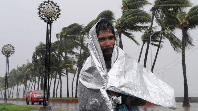A man walks through heavy wind and rain as Typhoon Rammasun barrels across Manila