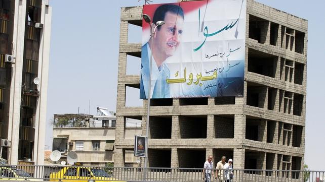 People walk past a huge billboard bearing a portrait of Mr Assad in Damascus