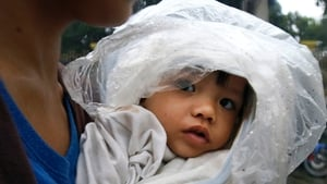 A child covered in plastic wrapping is carried by her mother in Manila