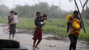 Filipino residents try to escape from strong winds brought by Typhoon Rammasun after it struck a fishing village in Las Pinas city