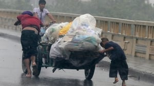 Residents push a cart with plastic covered belongings as they flee the strong winds and rain brought by Typhoon Rammasun