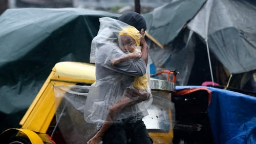 A father with his child covered under a plastic sheet flee the strong winds and rain brought by typhoon Rammasun in Manila