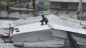 A man sits on a roof as strong winds batter the Philippines