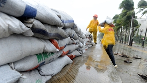 Workers build sand bag defences along the sea wall of Roxas Boulevard