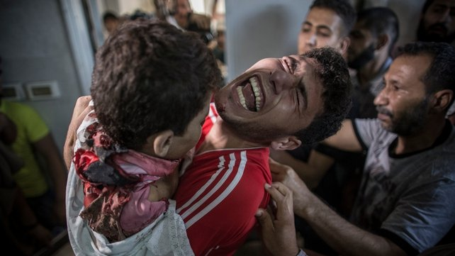 A Palestinian man cries as he holds the dead body of his young brother