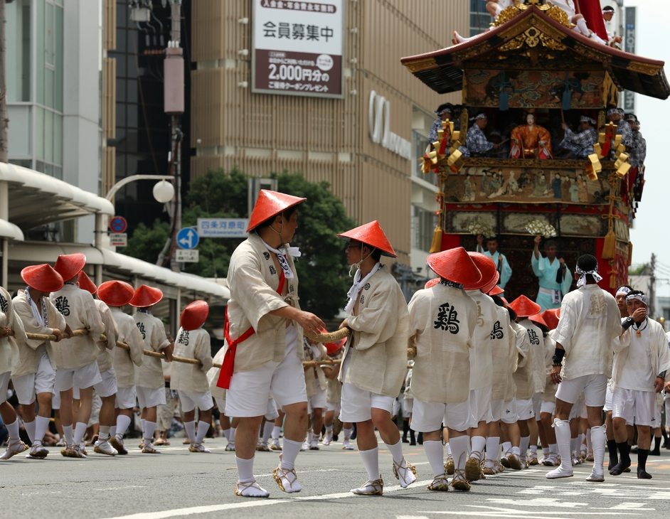 Japanese men dressed in traditional costumes tow a festival cart during the annual Kyoto Gion Festival