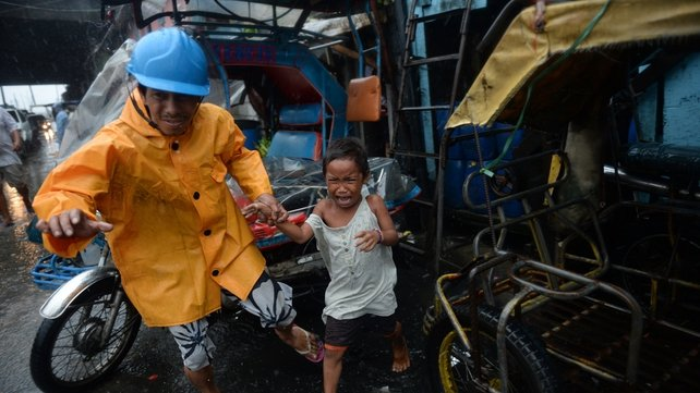 A village official leads a child to safety during the typhoon