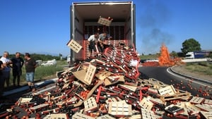 Protesters throw peaches from a Spanish truck and set fire to crates of fruit during a demonstration at a toll bridge on the A9 motorway in southern France, in a demonstration over fruit importation prices