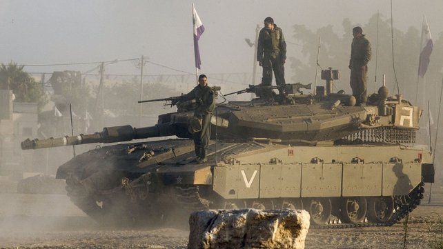 Israeli soldiers stand on their tank near Israel's border with the Gaza Strip ahead of the ceasefire
