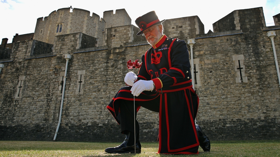 Crawford Butler, the longest serving Yeoman Warden at the Tower of London, poses with the first ceramic poppy to be 'planted' in the dry moat at Tower of London