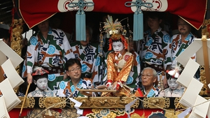 A sacred child (C) dressed in Japanese traditional costume cuts a Shimenawa, sacred wire rope during the annual Kyoto Gion Festival