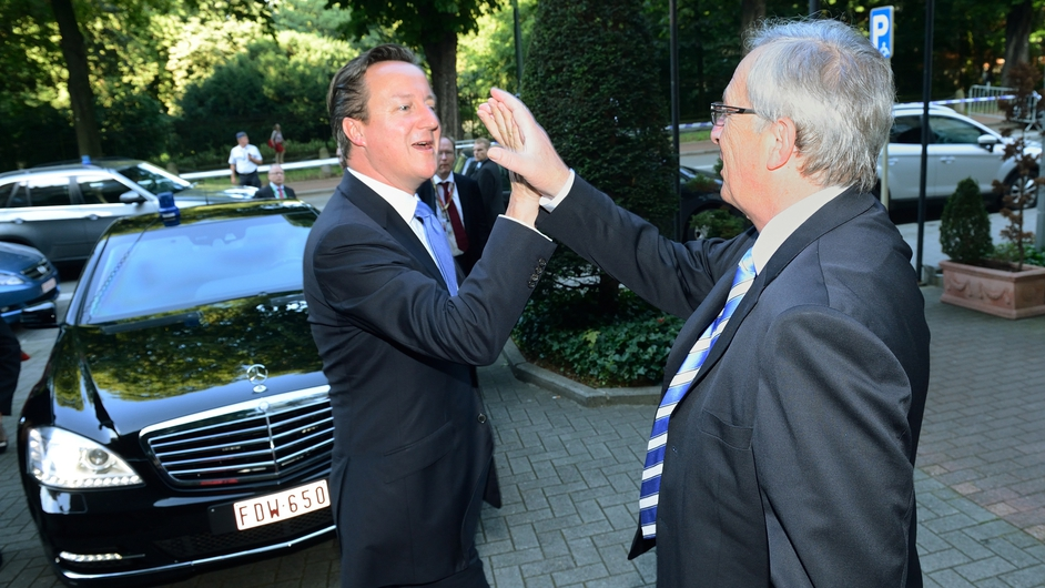 British Prime Minister David Cameron high fives European Commission President Jean-Claude Juncker in Brussels