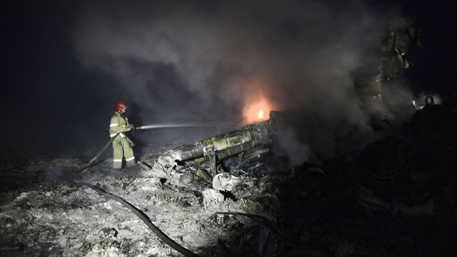 A firefighter tackles flames among the wreckage