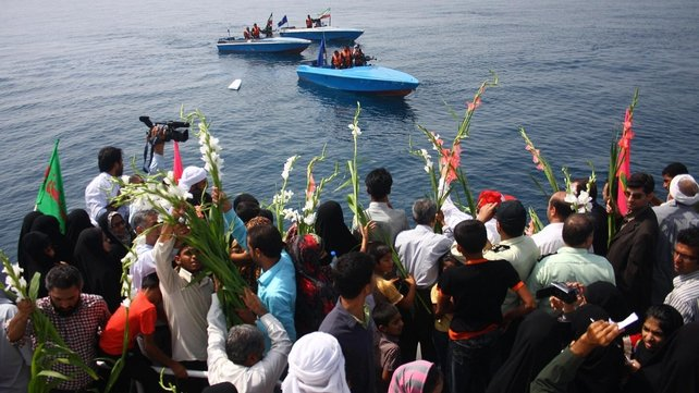 Relatives of people killed when Iran Air flight 655 was shot down throw flowers in the sea on the 21st anniversary of the incident