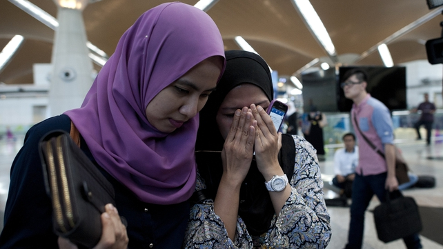 Relatives of a passenger who was on board Malaysia Airlines flight MH17 react to the news of the crash