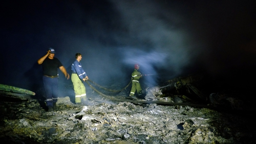 Firefighters spray water to extinguish a fire at the scene of the wreckage