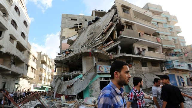 Palestinians inspect debris of a destroyed house following an Israeli airstrike in Gaza