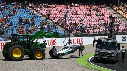 Lewis Hamilton's Mercedes is removed from the track following his early crash