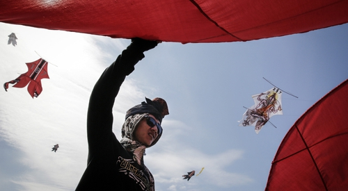 A participant prepares a traditional kite named Bebean during the Bali Kite Festival